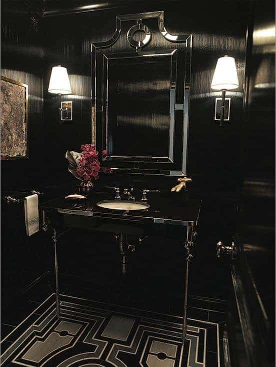 This black theme of the bathroom is a perfect pairing for the Victorian-style elements that are incorporated into the bathroom like the intricate patterns of the flooring matching the design of the vanity mirror flanked by wall lamps.
