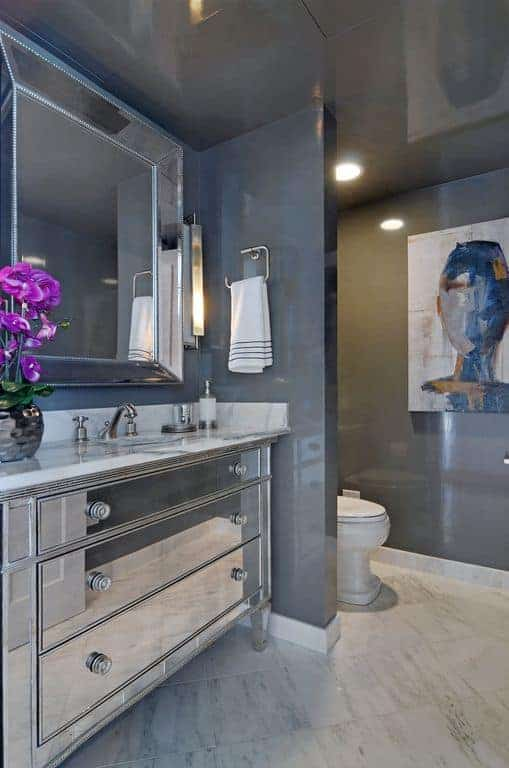 The mirrored drawers of the vanity matches with the vanity mirror. This stands out against the dark gray walls and ceiling that is warmed by the yellow recessed lights over the toilet that is adorned with a colorful large painting on its side wall.