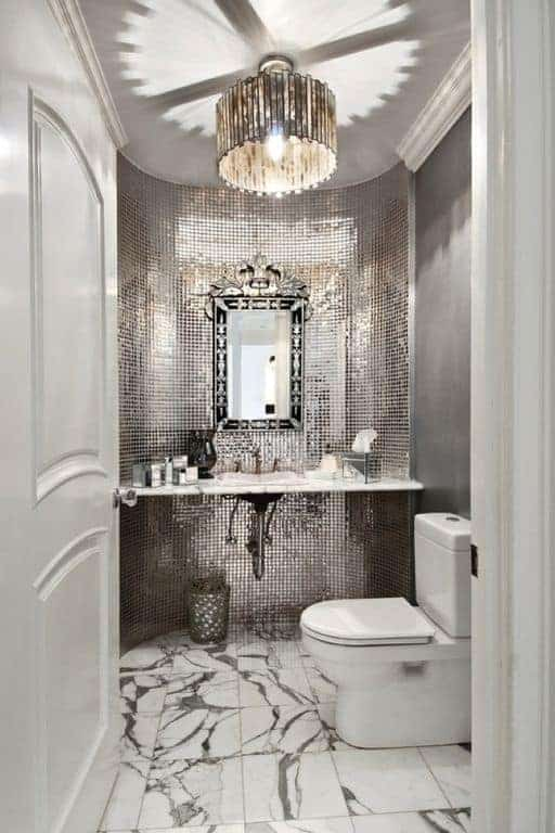 Upon entry of the white wooden door, you will be welcomed by a brilliant curved alcove that houses the vanity area within its shiny silver facade that provides a complex background for the white toilet and the white marble hanging sink.