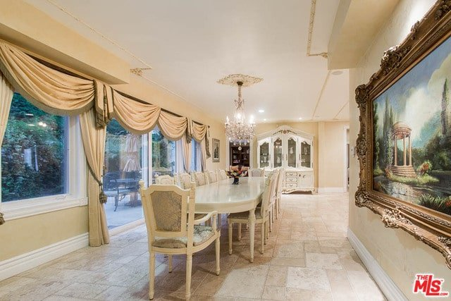 Victorian dining room with limestone flooring and beige walls adorned by a large landscape painting. It offers a classy white cabinet and a long dining set illuminated by a crystal chandelier.