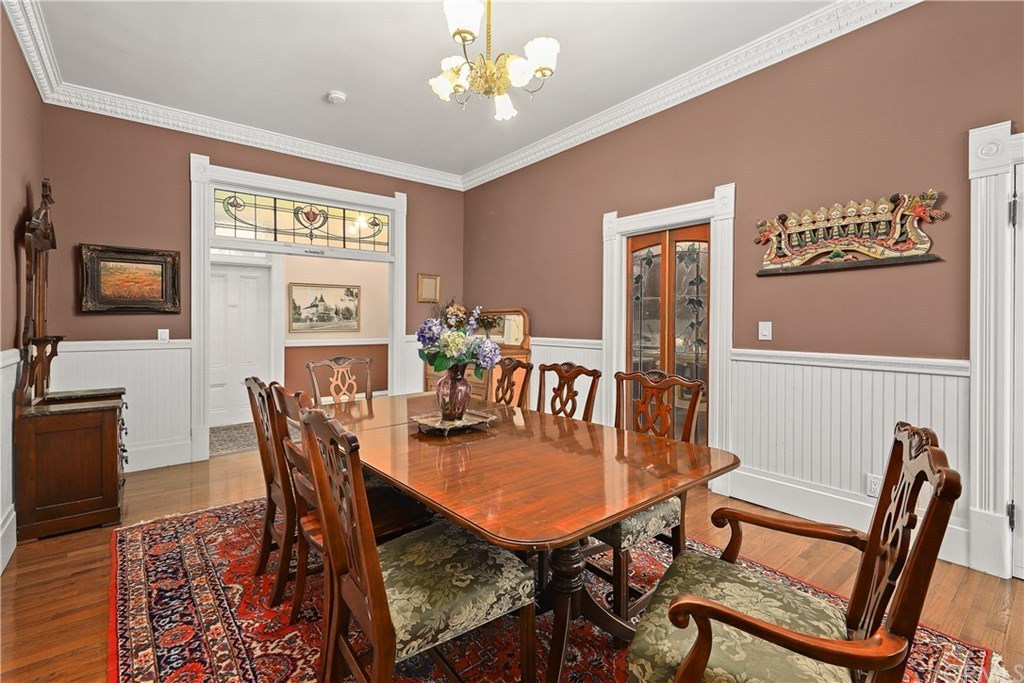 This dining room features a glossy dining table and floral cushioned chairs that sit on a red patterned rug over the hardwood flooring. It is decorated with a brass chandelier and gorgeous wall arts mounted above the white beadboard.