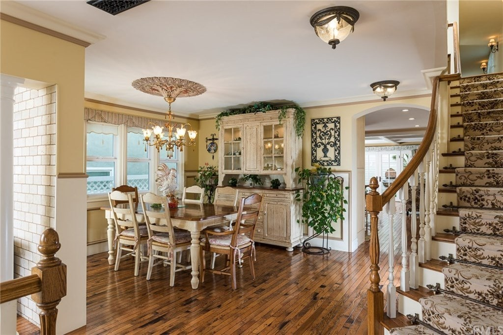 The classic dining room showcases distressed cream cabinets accented with creeping plants along with a wooden dining set lighted by an elegant brass chandelier. It has hardwood flooring and white framed windows inviting natural light in.