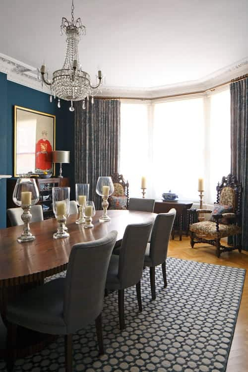 Sophisticated dining room features blue wall and full height windows allowing natural light in. It has a crystal chandelier and floral upholstered chairs facing the cozy dining set that sits on a dotted area rug.