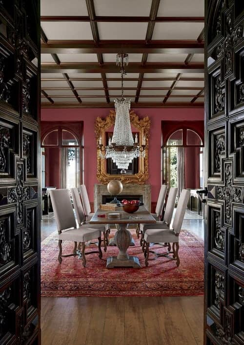 A black double door with intricate details opens to this red dining room boasting an ornate mirror above a fireplace and a crystal chandelier that hung over the natural wood table and gray upholstered chairs.
