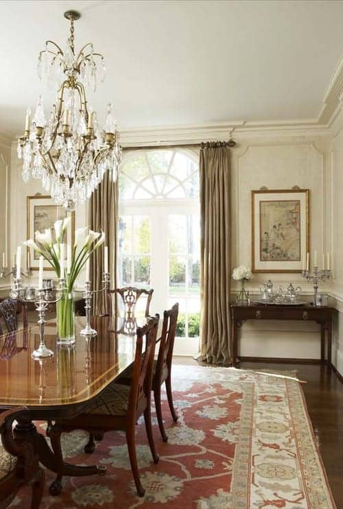 White dining room with full height wainscoting and a French door covered in taupe draperies. It includes a fabulous chandelier and a classy dining set that sits on a red area rug.
