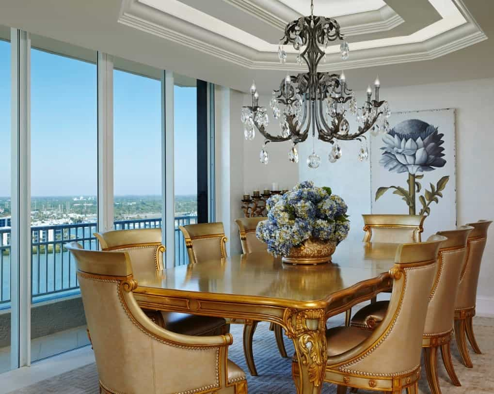 Luxury dining room features a lovely floral wall art and a fabulous chandelier that hung from the tray ceiling. It includes an elegant gold dining set placed across the floor to ceiling windows that bring plenty of natural light in.