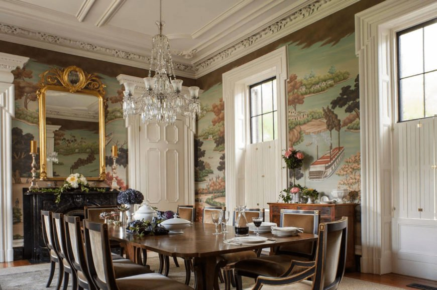A scenic mural adds a gorgeous accent to this Victorian dining room boasting a crystal chandelier and gold framed mirror mounted above the black buffet table.