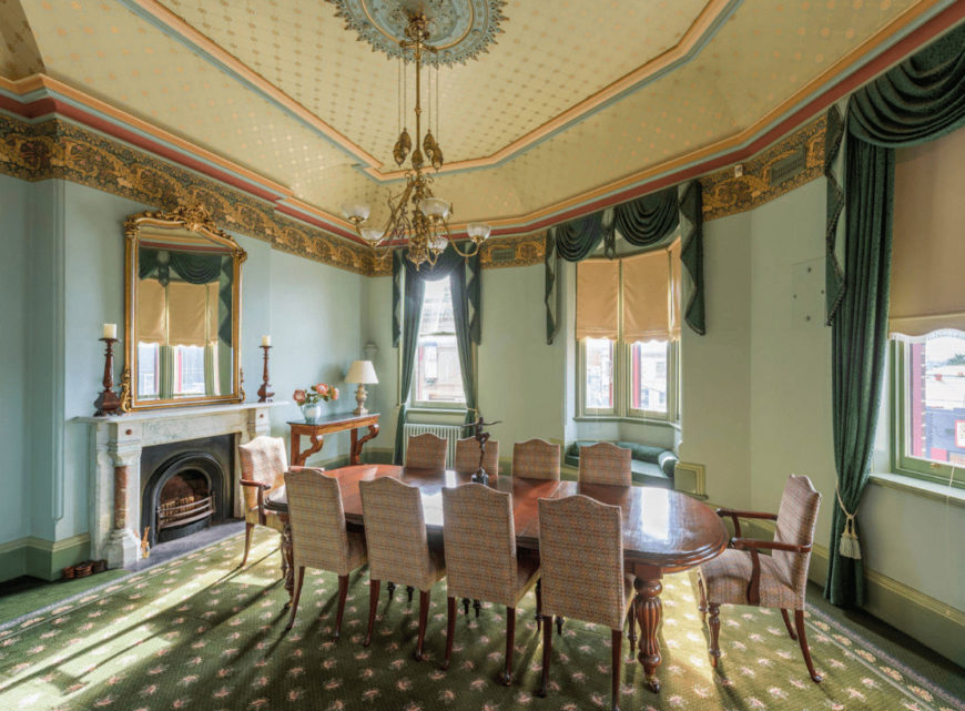 A dotted tray ceiling lined with multicolored crown moldings brings charm in this green dining room with a window seat nook and a wooden dining set accompanied by a console table and fireplace under the gold framed mirror.