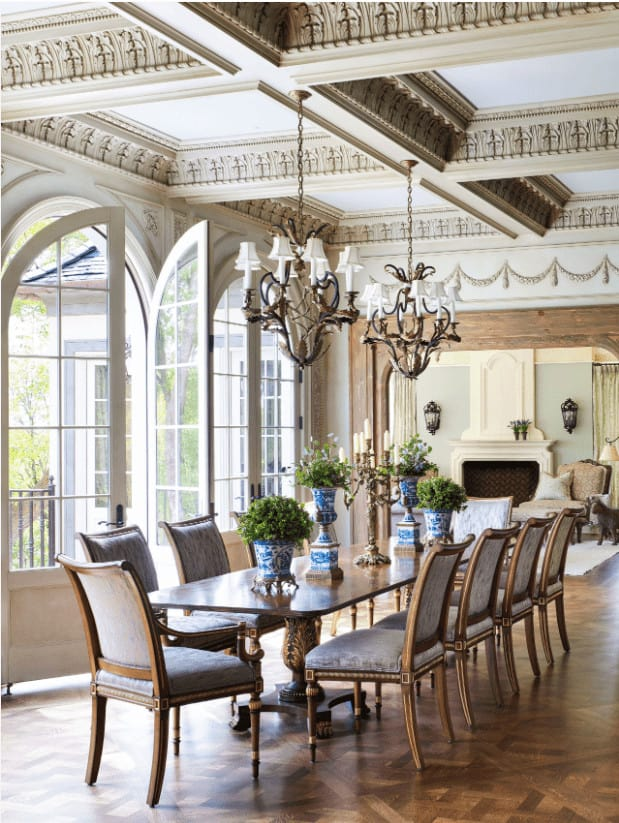 A pair of vintage chandeliers that hung from the stylish coffered ceiling illuminate this airy dining room showcasing a classy dining set and arched French doors that open to the balcony.