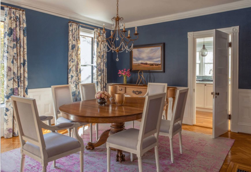 Victorian dining room showcases a copper chandelier and landscape wall art mounted on the blue wall that's clad in white wainscoting. It includes a wooden dining table and white cushioned chairs over a distressed pink rug.
