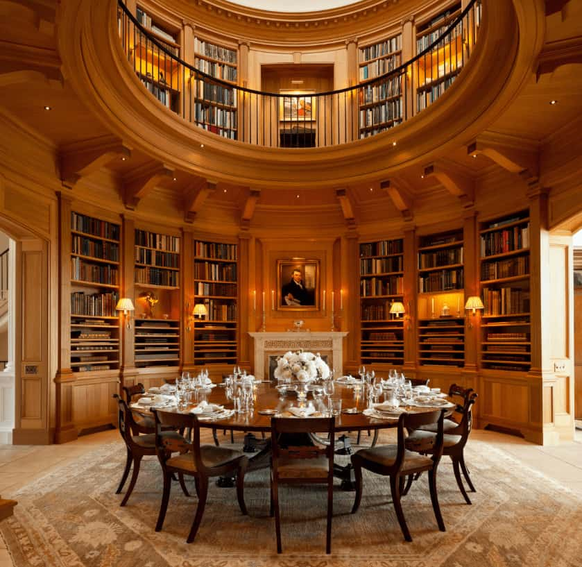 Deluxe dining room with a dark wood dining set and an elegant fireplace fixed in between built-in bookshelves. It is illuminated by wall sconces and recessed lights mounted on the round ceiling.