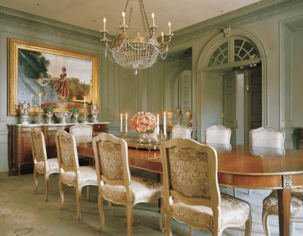 A large gold framed photo hangs over the wooden buffet table in this dining room with a candle chandelier and oval dining table surrounded by floral upholstered chairs.