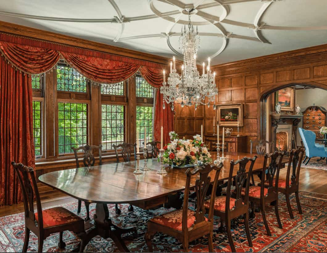 Sophisticated dining room with stylish white ceiling and wooden framed windows dressed in classy red drapes and valances. It includes a glamorous chandelier and wooden dining for ten.