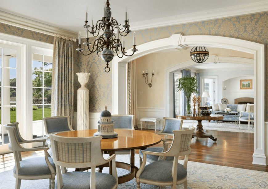 Fresh dining room clad in patterned wallpaper that matches the draperies covering the white framed windows. It has an ornate chandelier and a round dining table paired with light blue cushioned chairs that sit on a charming area rug.
