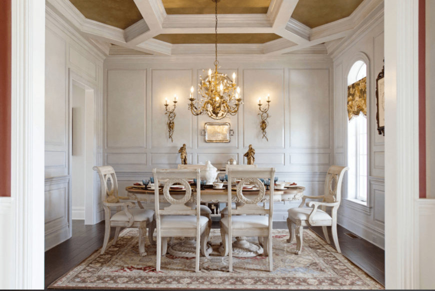 White dining room with gold accents from the sconces, chandelier and coffered tray ceiling. It has a light wood dining set and a floral area rug that lays on the wood plank flooring.