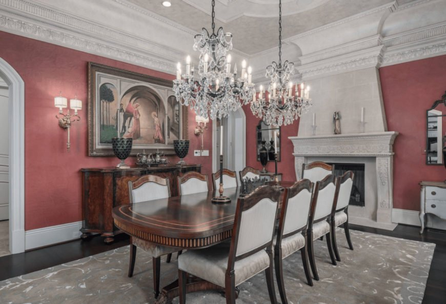 Red dining room decorated with a framed photo and fancy chandeliers that hung over the wooden dining set. It has an ornate fireplace and a console table topped with black vases.