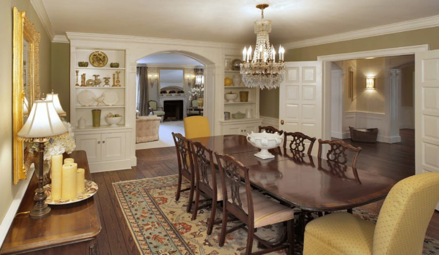 The charming dining room showcases white built-in shelving with an open archway in the middle along with a crystal chandelier that hung over the dark wood dining table surrounded by pink striped cushioned and yellow dotted chairs.