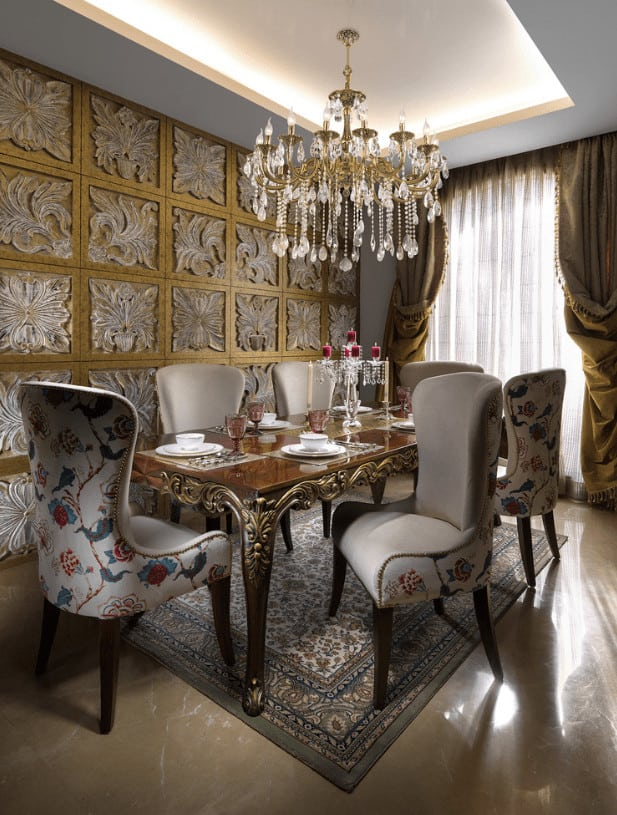 A stylish paneled wall adds an eye-catching texture in this elegant dining room with marble flooring and full height windows dressed in yellow and white sheer curtains.