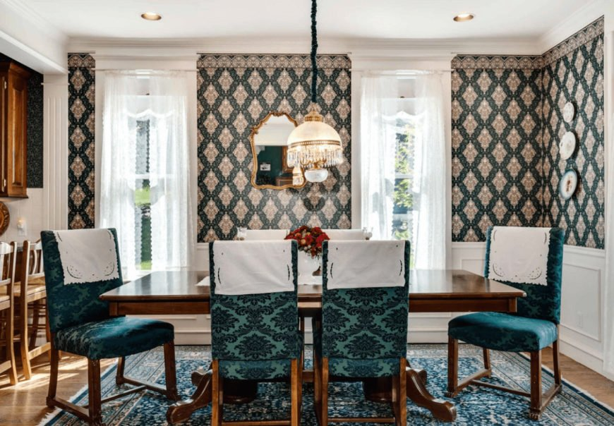 Victorian dining room designed with decorative plates and a gold framed mirror mounted above the white wainscoting. It has a wooden dining table and green patterned chairs complementing with the area rug that lays on the hardwood flooring.