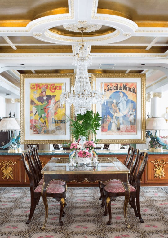 Gorgeous dining room designed with large wall arts mounted on the mirrored wall and a stylish round tray ceiling with a hanging crystal chandelier.
