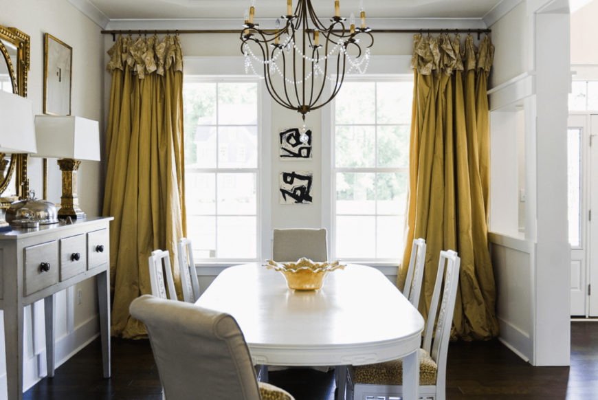White dining area accented with gold mirror and yellow curtains covering the white framed windows. It has a vintage chandelier and cushioned chairs surrounding an oval table topped with a decorative bowl.