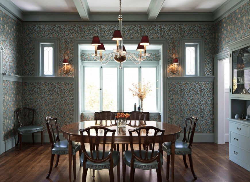 Clad in green floral wallpaper, this dining room offers a display cabinet and cozy dining set lighted by a glass chandelier and matching sconces.
