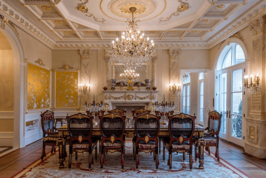 Deluxe dining room features a white fireplace with gold accent and gorgeous dining set lighted by a candle chandelier that hung from the coffered tray ceiling showcasing an elegant design.