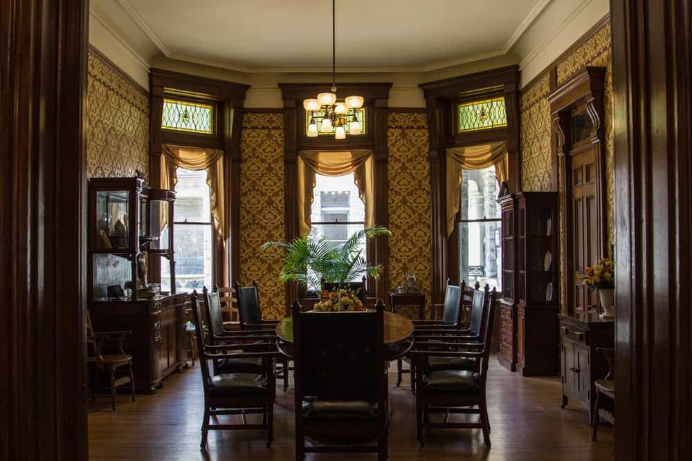Victorian dining room showcases hardwood flooring and glass paneled windows dressed in yellow valances. It has a warm chandelier and black dining set situated in between display cabinets.