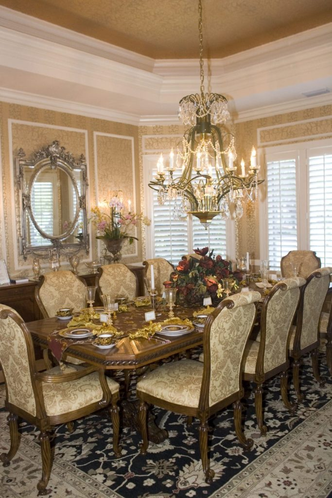 This dining room offers a classy dining set and a gorgeous candle chandelier that hung from the tray ceiling. It includes a black area rug and an ornate mirror mounted above the wooden buffet table.