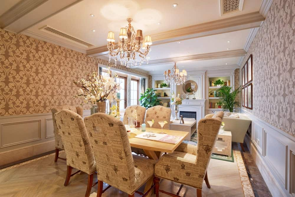 Clad in classy patterned wallpaper and white wainscoting, this dining room features a wooden dining table and printed upholstered chairs on a chevron flooring illuminated by a fancy chandelier and recessed ceiling lights.