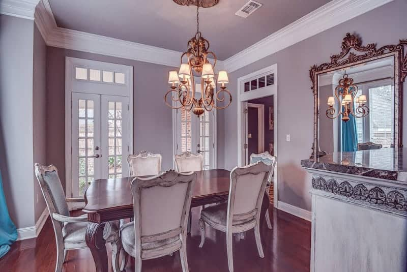 Victorian dining room with a vintage chandelier and wooden dining table paired with distressed white chairs over the rich hardwood flooring. It has gray walls and a pair of French doors that lead out to the yard.