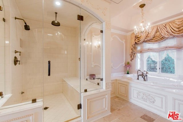 Luxury primary bathroom with a walk-in shower fitted with a tiled bench and bronze fixtures. It is completed with a deep soaking tub by the glazed window dressed in classy valances.
