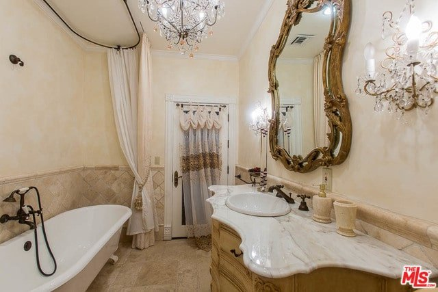 A fabulous crystal chandelier along with matching sconces illuminate this primary bathroom boasting a tub and shower combo along with a marble top vanity that's paired with a stylish carved wood mirror.