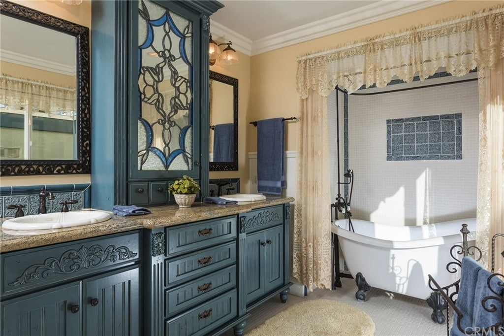 The victorian primary bathroom features a dual sink vanity topped with a granite countertop and a blue cabinet with a stained glass door flanked by stylish mirrors. It is accompanied by a clawfoot tub on the side situated on the inset wall that's dressed in lace curtains.