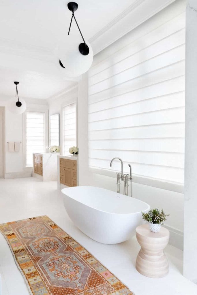 A lovely printed runner stands out in this white primary bathroom with tiled flooring and plenty of glazed windows covered in translucent roller blinds. It features a freestanding tub with a round stool on the side lighted by sleek pendants.