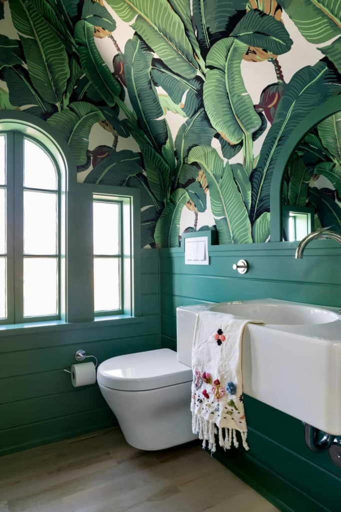 Tropical wallpaper adds character in this green Victorian bathroom showcasing a modern toilet and a wall-mounted sink against the shiplap wall. It has light hardwood flooring and glazed windows inviting natural light in.