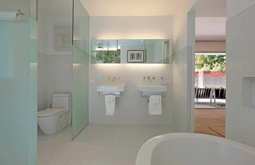 White master bathroom offers a toilet area along with his and her wall mount sinks fitted with towel racks. It includes a lovely black framed photo that's reflected in the medicine cabinets with strip lights.