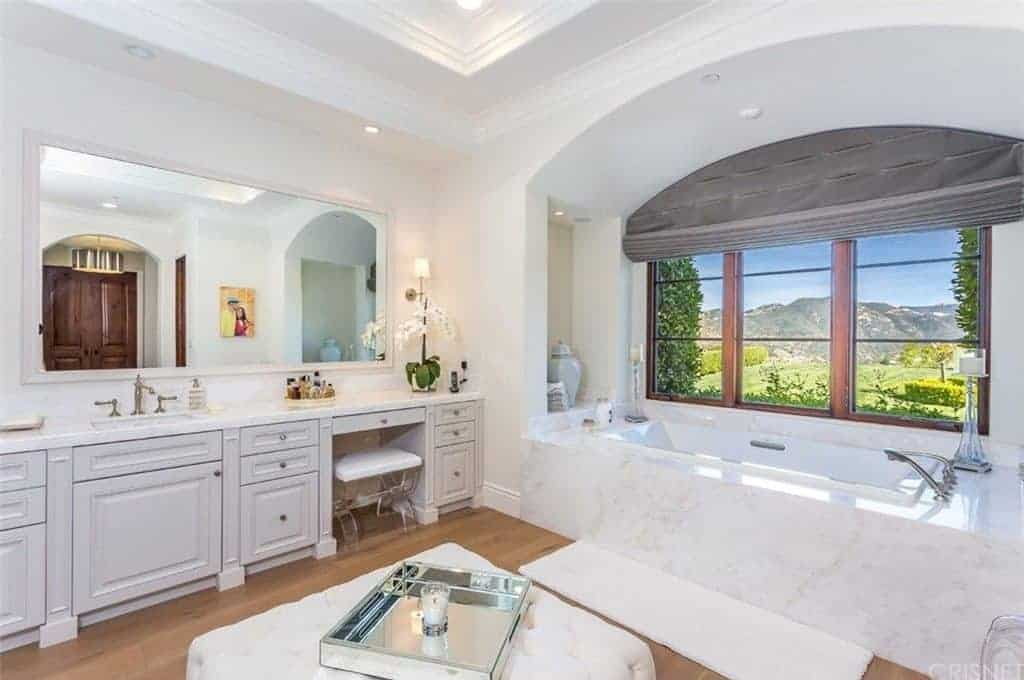 Elegant master bathroom features a white tufted ottoman and a lengthy vanity along with an alcove bathtub with wooden framed windows overlooking a stunning mountain view.