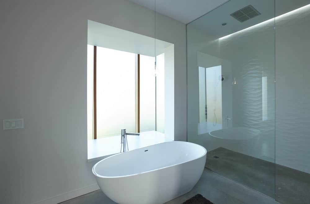 Sleek bathroom with a minimalist design. It has a walk-in shower enclosed in frameless glass and a freestanding tub by the glazed window and over concrete flooring.