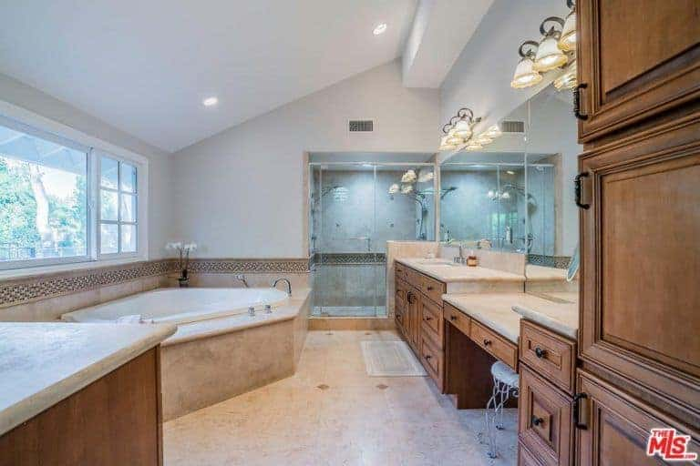 Classy bathroom with a walk-in shower and corner tub fixed across the wooden vanity that's illuminated by vintage sconces and recessed lights mounted on the shed ceiling.