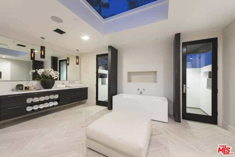 Spacious master bathroom showcases a freestanding tub and white ottoman on herringbone flooring beautifully contrasted by a floating vanity and dark wood doors.