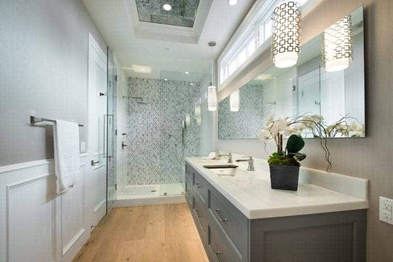 Stylish master bathroom with a white and gray color palette that goes well with the light hardwood flooring. It has marble top vanity and a stainless steel towel rack mounted above the white wainscoting.