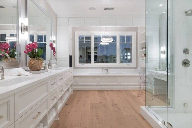 White master bathroom with a walk-in shower and drop in tub lighted by a classy round pendant. It includes two vanities and a glass chair that sits on natural hardwood flooring.