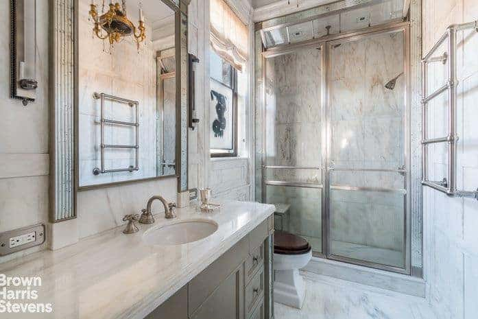 A classy chandelier is reflected in the mirror that hung above the gray vanity in this master bathroom with a toilet and walk-in shower enclosed in glass.