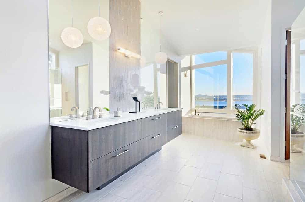 Bright bathroom illuminated by round pendants that hung over the floating sink vanity along with natural light from the glazed windows bringing plenty of natural light in.