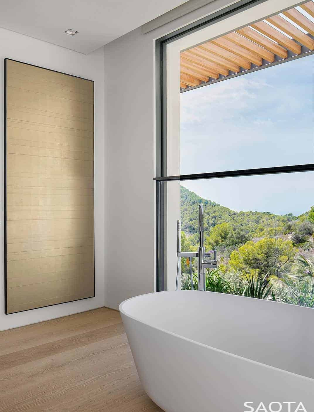 Small white bathroom showcases a freestanding bathtub that sits on light hardwood flooring. It is across a panoramic window overlooking a serene outdoor view.
