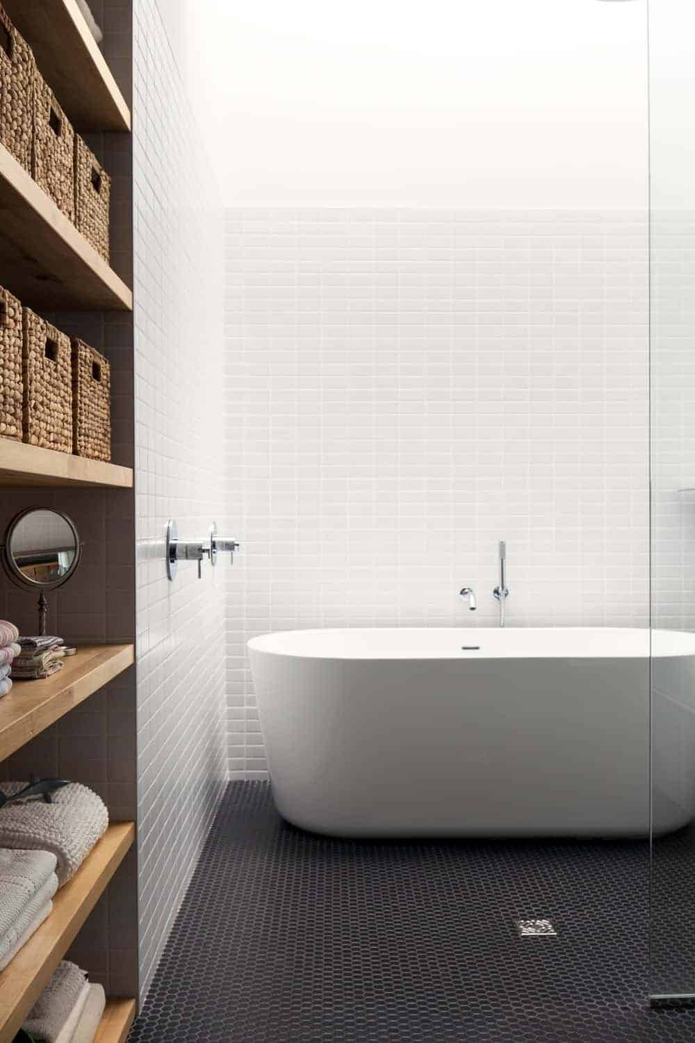 Modern bathroom with a freestanding tub placed against the white subway tile backsplash that's beautifully contrasted by black hex tile flooring. There's built-in shelving on the side filled with storage boxes and towels.