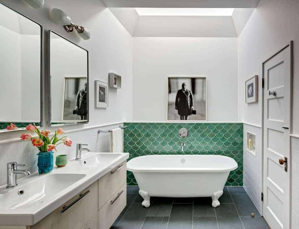 Clean, white bathroom accented by green tile backsplash topped with an interesting photo frame. It has a clawfoot tub and dual sink vanity paired with rectangular mirrors.