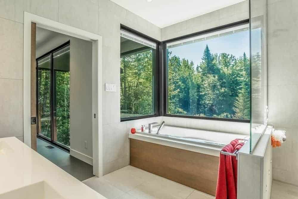 Fresh bathroom with a view of pine trees from the lush green forest through its glazed windows. It has a drop in tub clad in light wood panel blending perfectly with the white tiled walls and flooring.