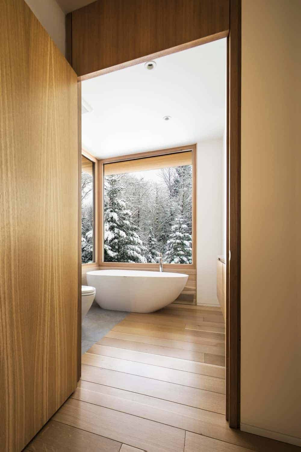A wooden door opens to this cozy bathroom with a toilet and freestanding tub over wood plank flooring and against the white walls.